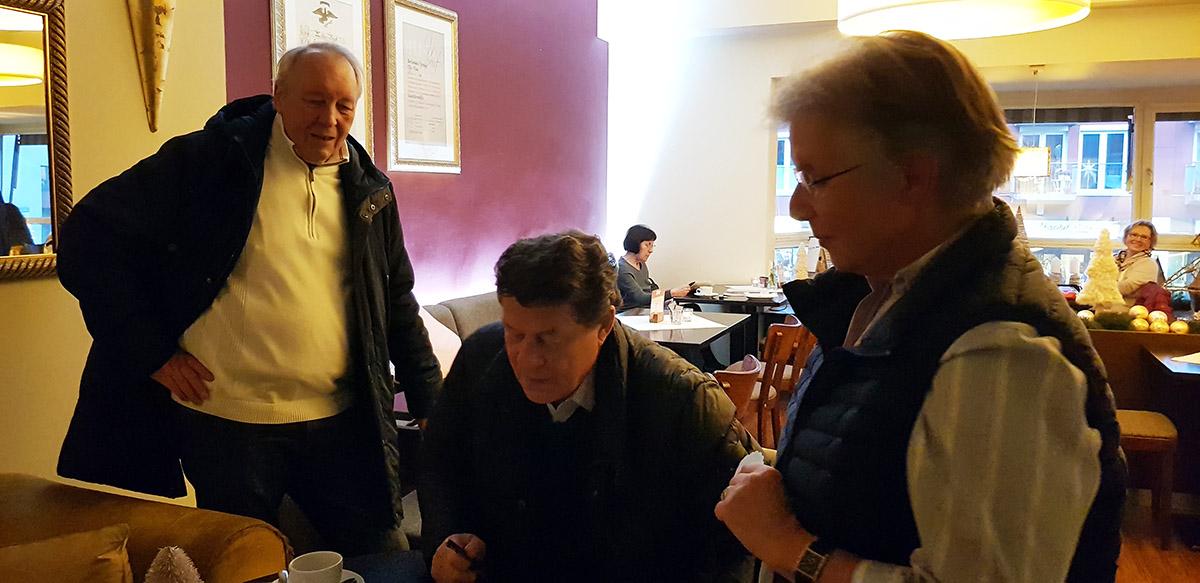 Hier sehen wir Rolf Landes, der das Treffen mit Otto Rehagel vorbereitete und eine Frau, die ein Autogramm für ihren Mann bekam.